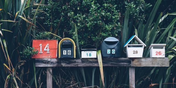 row of six multicolored mailboxes